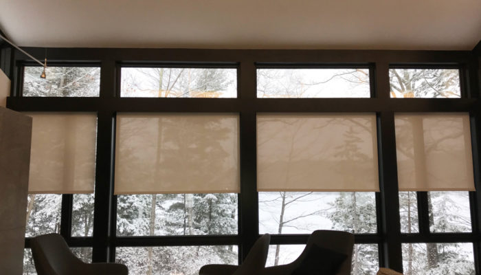 This Is A Picture Of A Living Room That Looks Out Onto A Winter Wonderland. This Room Has Large Windows Which Feature Specialty Shades On A Portion Of The Windows.