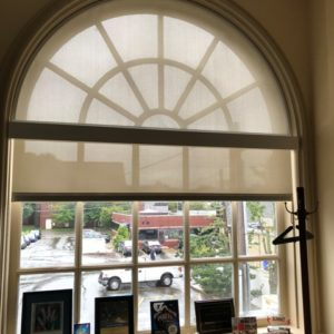 This Is A Picture Of A Window With A Rounded Top Featuring A Custom Shade To Fit The Window.